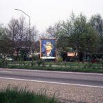 Zelfportret met grijze vilthoed als billboard langs de weg